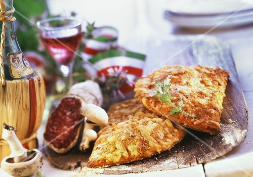 Pizza turnovers on wooden paddle; ingredients; Italian flag