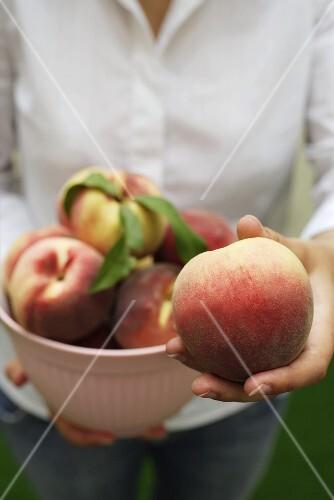 Woman holding fresh peaches