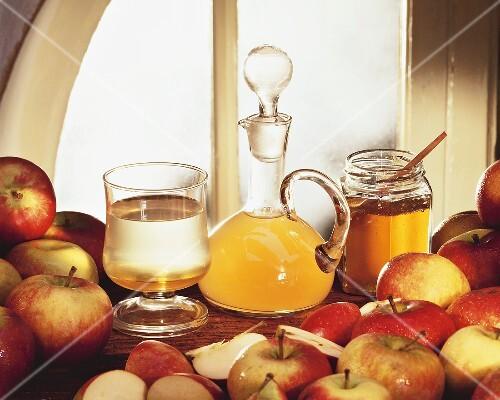 Still life with apple vinegar, honey and fresh apples
