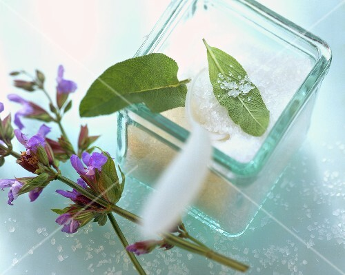 Salt with sage leaves in a glass container, with sage flowers