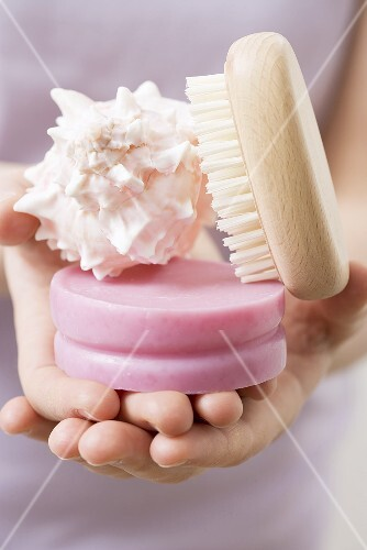 Hands holding soap, shell and brush