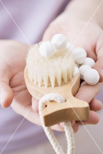 Hands holding brush and bath balls