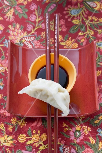 Soy sauce in small dish, chopsticks and wonton on dish