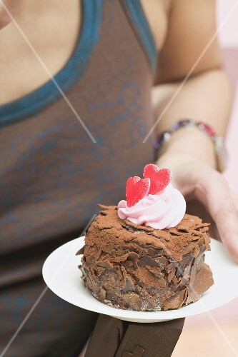 Woman holding small chocolate cake with red hearts