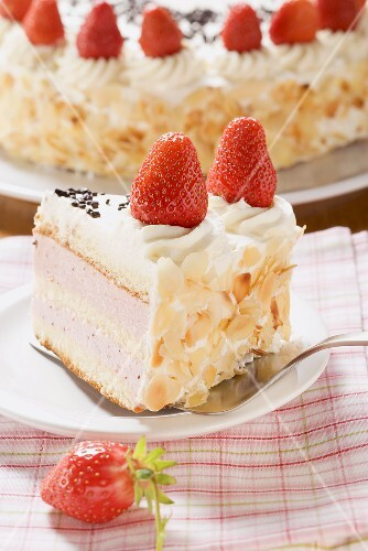 Piece of strawberry cream cake with flaked almonds on server
