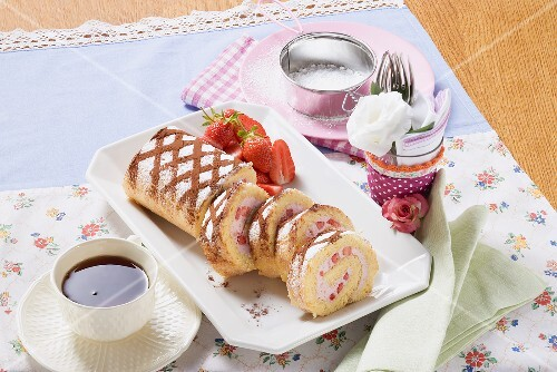 Sponge roll with strawberries, partly sliced, cup of coffee