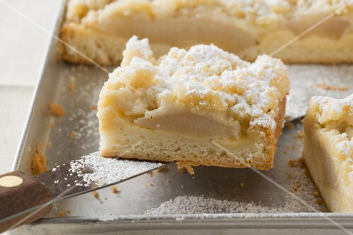 Pear crumble cake on baking tray (close-up)