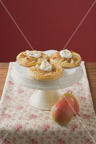 Pear tartlets with cream on cake stand