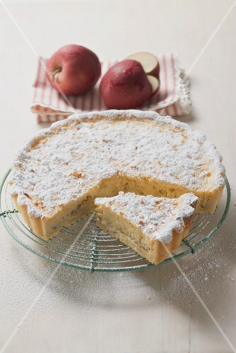Apple tart with icing sugar, a piece cut, on cake rack