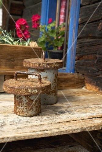 Rusty weights on wooden table outside a wooden house