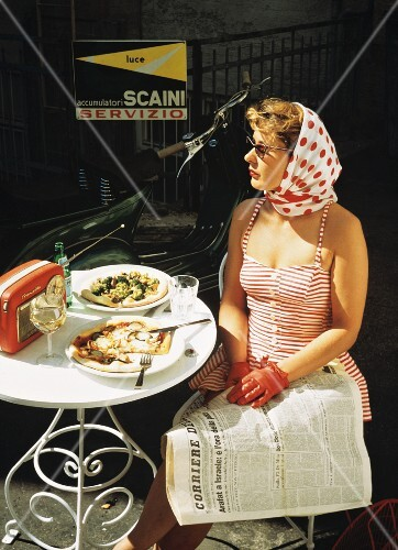 Woman at bistro table with two pizzas