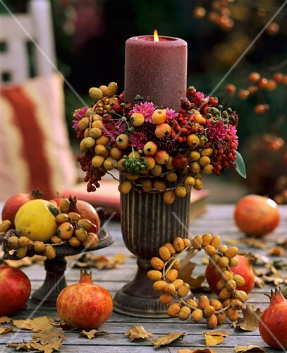 A burning candle on a table with autumn decorations