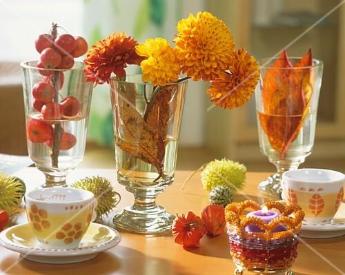 Ornamental apples, chrysanthemums & foliage in wine glasses