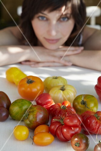 Various kinds of tomatoes, young woman in background