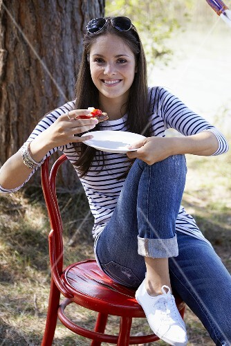 Young woman eating tomato and goat cheese crostini