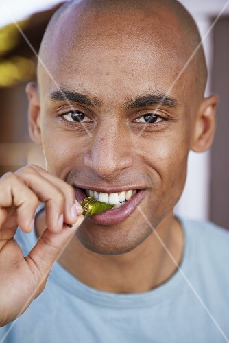 Young man biting into a pepper
