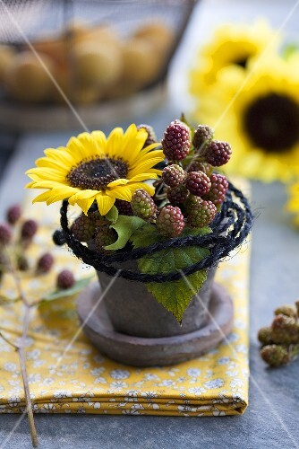 Decoration comprising sunflowers and sprigs of blackberries