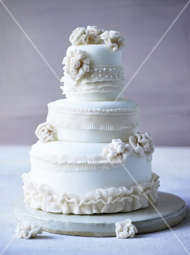 Three-tiered white wedding cake decorated with fondant flowers