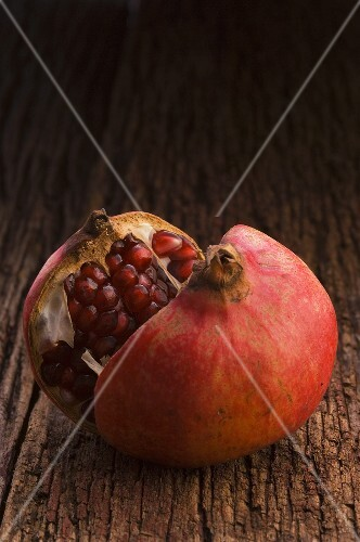 Pomegranate, halved, on wooden background