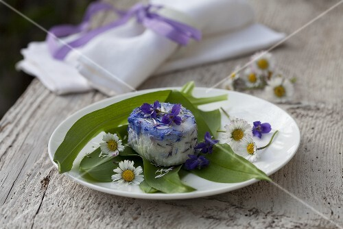 Goat's cheese with violets and daisies on ramsons (wild garlic)