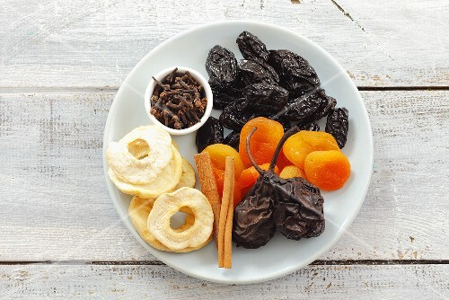 Assorted dried fruit, cinnamon sticks and cloves on plate