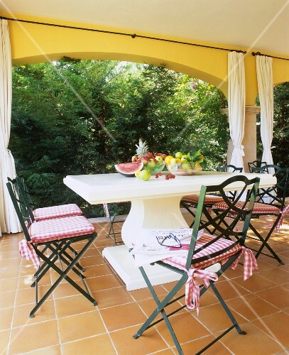 Various fruits on a stone table with a curved column foot and country house style chairs on a terrace