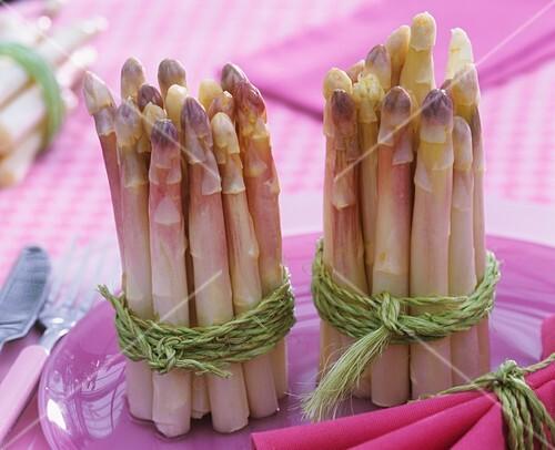 Bundles of white asparagus on purple plate