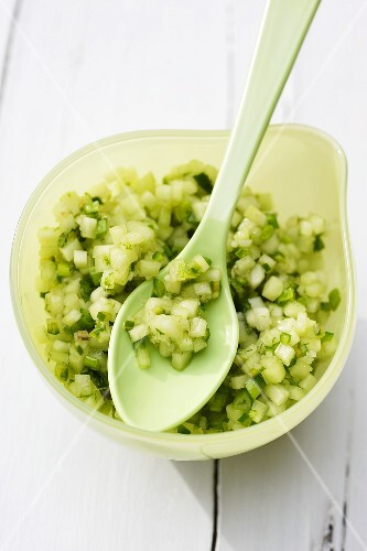 A bowl of cucumber salsa with a spoon
