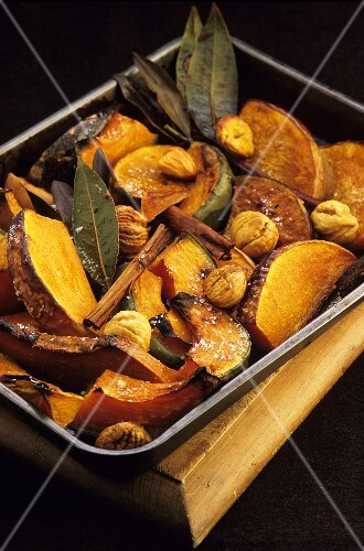 Pumpkin with chestnuts and cinnamon sticks in roasting tin