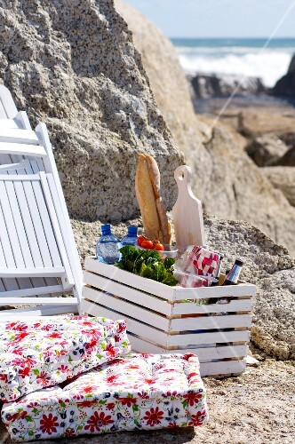 Box of food, beach chairs and cushions by rocks