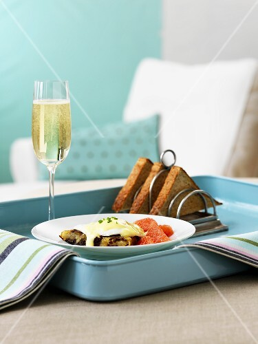 Hash browns with a poached egg, toast and a glass of champagne