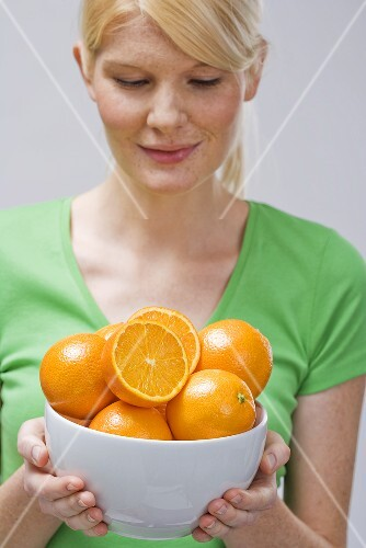Woman holding bowl of fresh oranges