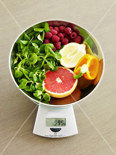 Fruit and vegetables (rich in vitamin C) on scales