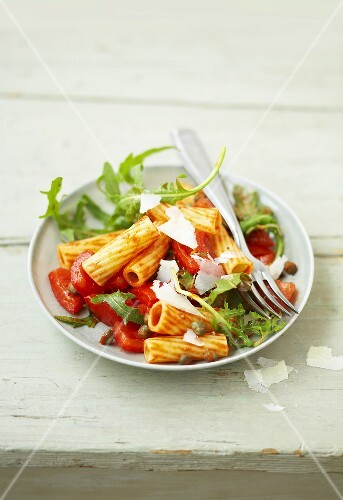 Spicy pasta salad with tomatoes, capers, rocket and Parmesan