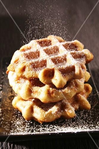 Sprinkling waffles with icing sugar