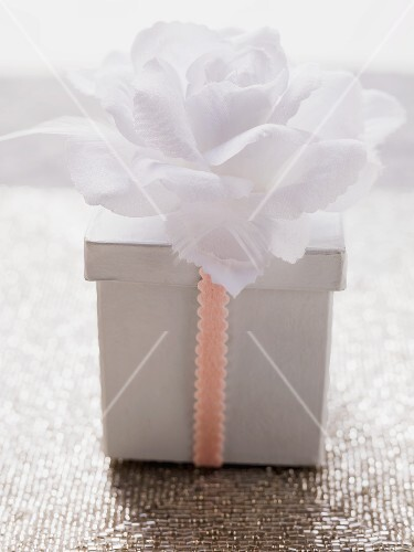 Box with ribbon and white flower