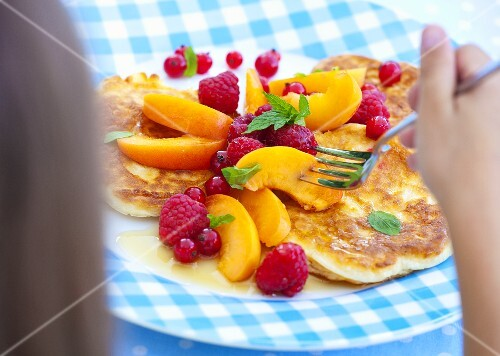 A child eating pancakes with fresh fruit