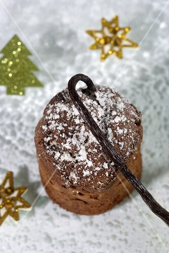 A Christmas chocolate cake with icing sugar and a vanilla pod