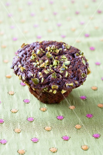 A muffin with pistachios and chocolate chips