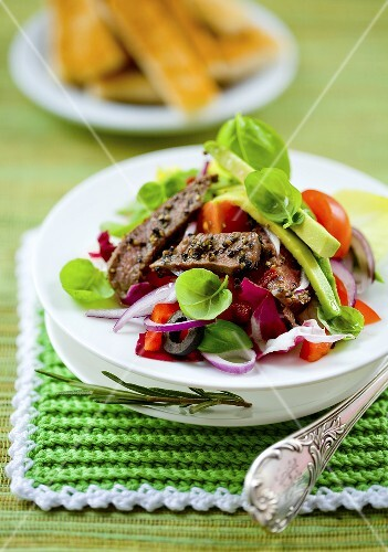 A colourful mixed salad with beef strips and avocado