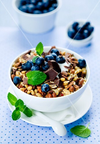 A bowl of muesli with chocolate pieces, blueberries and mint