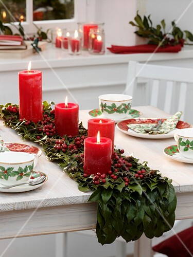 Table runner of holly leaves with four red candles