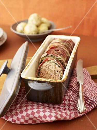 Oven-baked meatloaf wrapped in savoy cabbage and bacon