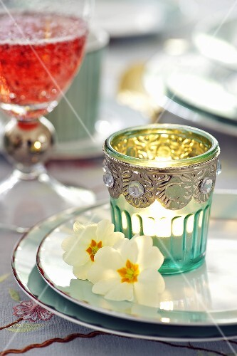 Easter place-setting with candle in glass and primroses