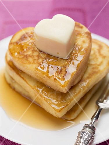 Heart-shaped pancakes with maple syrup and butter