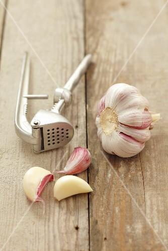 Garlic and a garlic press on a wooden surface