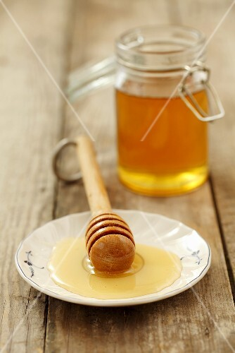 Honey on a plate with a honey spoon with a jar of honey in the background