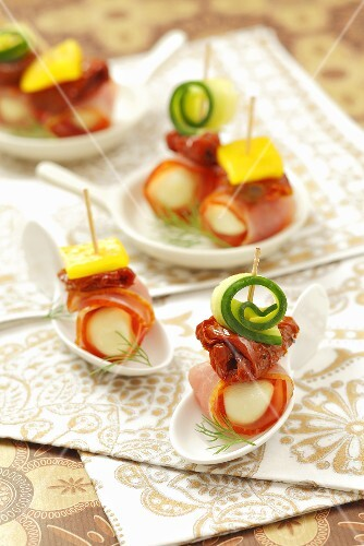 Mozzarella balls wrapped in ham with dried tomatoes and cucumber
