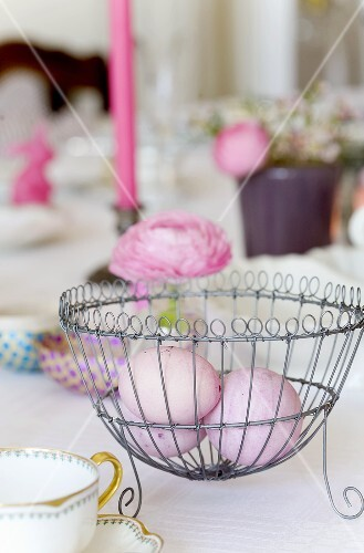 Pink Easter eggs in a wire basket on a table decorated for Easter