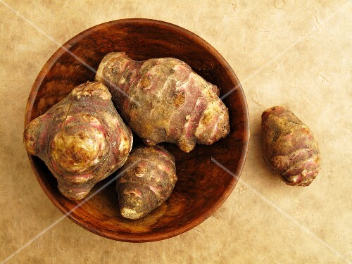 Jerusalem artichokes in a wooden bowl and to the side